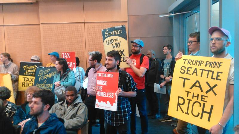 People pack city hall for a hearing on a proposed income tax