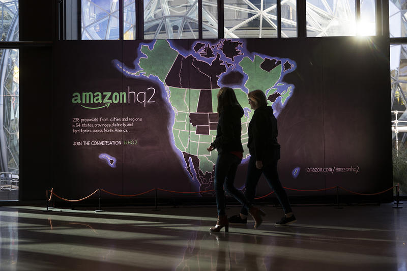 Amazon employees walk in front of a map highlighting 238 cities that submitted bids for Amazon's second headquarters in the lobby of the Day 1 building on Tuesday, October 24, 2017, in Seattle.