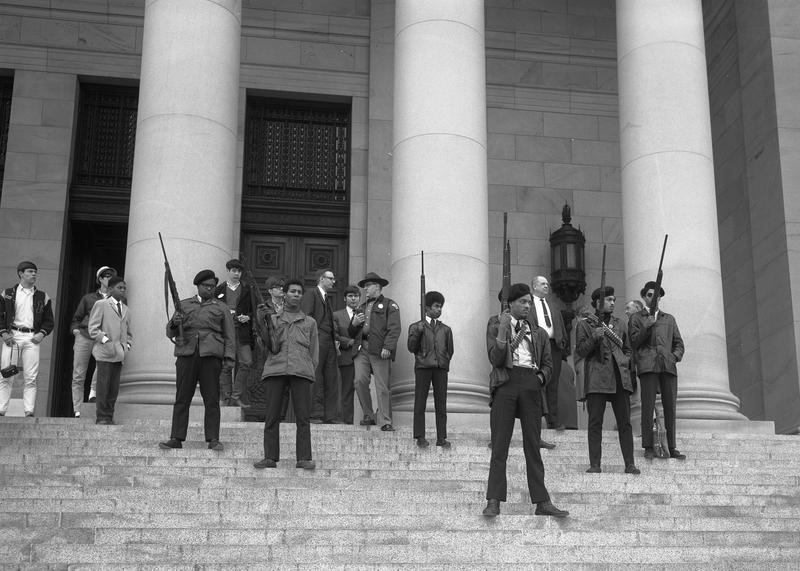 Elmer Dixon and other Seattle Black Panthers gather on the steps of the Capitol in Olympia on February 28, 1969, to protest a bill aiming to it a crime to exhibit firearms with 'an intent to intimidate others.'