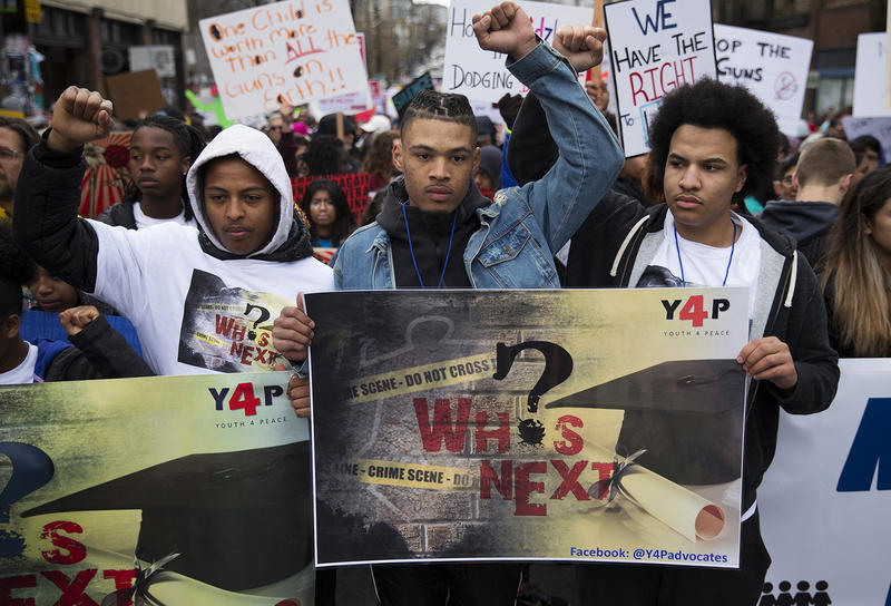 Gregory Pleasant, 17, center, and Elijah Lewis, 18, right, raise their fists in the air before the start of March For Our Lives Seattle on Saturday, March 24, 2018, in Seattle.