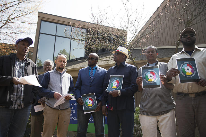 From left, Abdi Adan and Tawfik Maudah read over the  demands that they will make before entering Tukwila City Hall with community members and business owners on Thursday, April 19, 2018, in Tukwila.