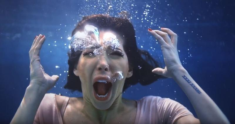 Screenshot from the music video for the song 'Leave Them' features childhood sexual assault survivors scream underwater as a way to highlight their silence.