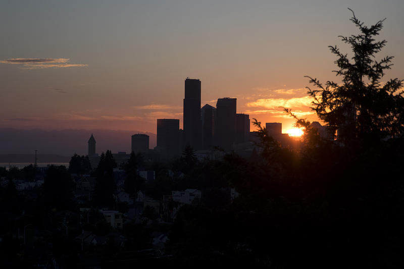The sun sets behind downtown Seattle on Tuesday, June 20, 2018