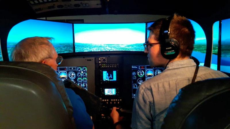 KUOW reporter Casey Martin, right, gets instruction with Spence Campbell of Aviation Training Center on how to use a flight simulator to fly a Bombardier Q400 on Tuesday, August 14, 2018.