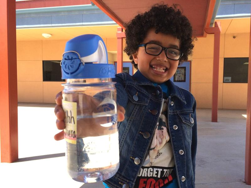 First-grader Shiloh Rivera holds up a reusable water bottle donated to every student at his Arvin school as part of an advocacy campaign called Agua4All.