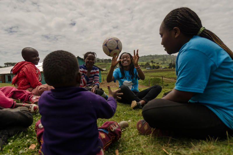 Sally Gacheru, center, tosses a ball to a child in Sakutiek, Kenya. Gacheru, who was born in Kenya but moved to St. Louis four years ago, was part of a service trip back home for fellow immigrant teens this month.