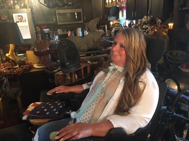 A woman injured in a car accident sits in a wheelchair in her home.