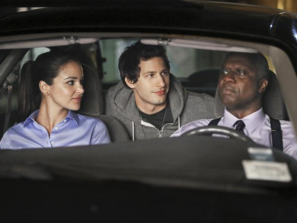 Capt. Ray Holt (Andre Braugher, right) leads detectives Jake Peralta (Andy Samberg) and Amy Santiago (Melissa Fumero) on a police stakeout in <em>Brooklyn Nine-Nine</em>.