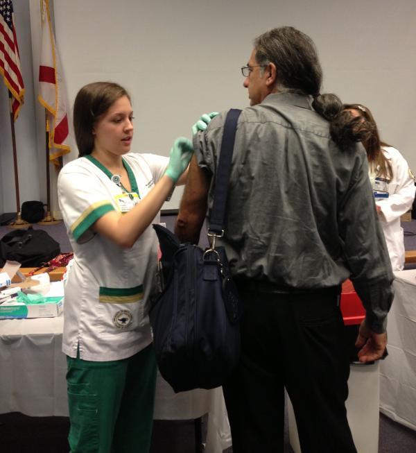 WUSF's Steve Newborn gets a free flu shot from a USF nursing student.