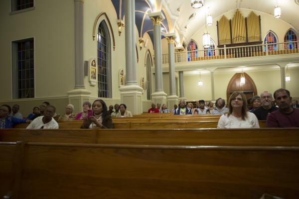 Anita Battis (far left) and Margaret Cortez (far right) among the congregation at a healing mass.