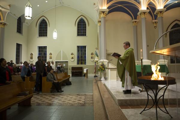 Father Michael Miceli continues his sermon while wood from the old bathroom building burns.