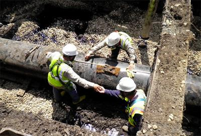 Workers measure pipe before cutting and removing the section from the Enbridge pipeline oil spill site near Marshall, Michigan.  This photo was taken on August 6th, 2010.