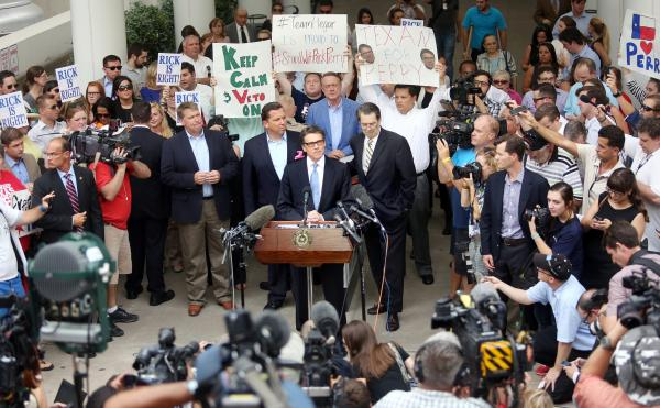 Governor Rick Perry speaks to the press and supporters outside the Travis County Criminal Justice Complex on August 19, 2014.