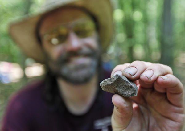 Daniel Sayers has been working for more than a decade in Great Dismal Swamp; here, in 2011, he displays a fire-cracked rock from a dig site. His new book pieces together the stories of those who once lived in settlements scattered on patches of dry land in the swamp.