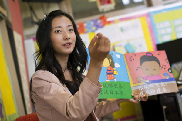 Teacher Tingting Mei reads a book in Mandarin to kindergarteners. Mei says repetition is how she helps her students master the language.