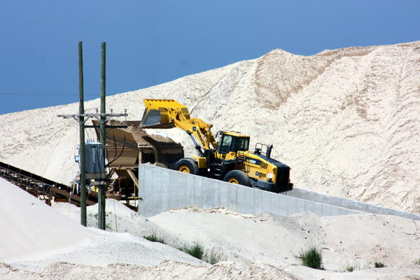 A dump truck moves sand around the mine's property.