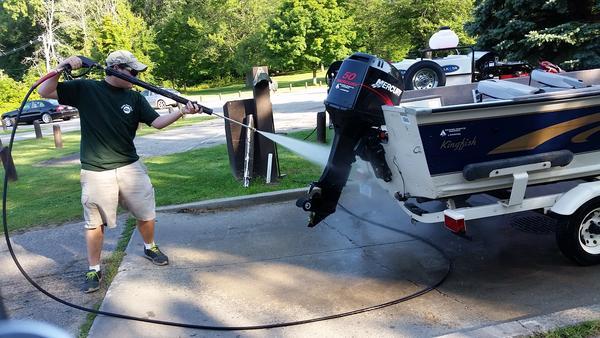 Michael Guthard sprays down Mark Stevens' boat.