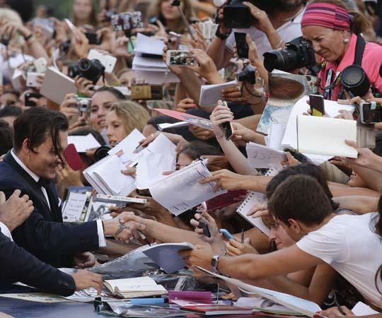 """Actor Johnny Depp signs autographs for his fans as he arrives for the screening of the movie """"Black Mass"""" at the 72nd edition of the Venice Film Festival in Venice, Italy, Friday. (Andrew Medichini/AP)"""