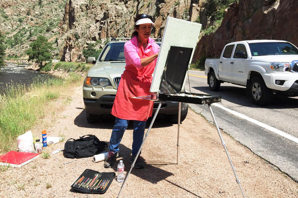 Plein air artist Marie Massey says the river below drowns out the sounds of the cars that pass as she paints the Poudre River. with cars