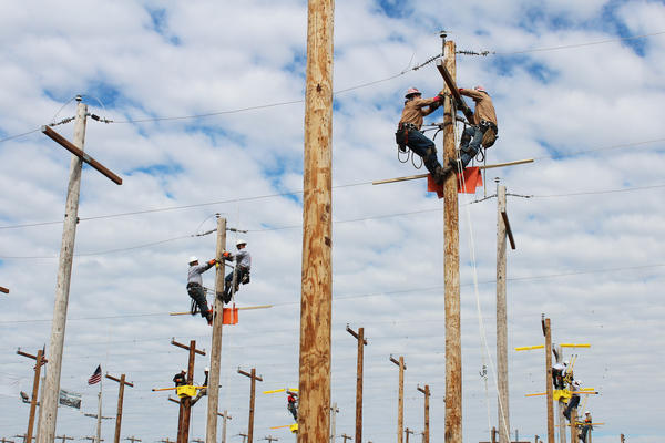 Lineman rodeo contestants participate in an event that simulates an electrical problem to be fixed in Bonner Springs, Kan. The challenge was announced the night before.