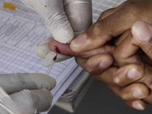A patient undergoes a pin prick blood test for HIV.