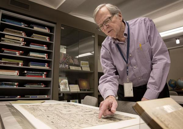 Boston Public Library map curator Ronald Grim on Friday looks over a copy of the  Carte Geographique de Nouvelle France, compiled in 1612 by explorer Samuel de Champlain. (Robin Lubbock/WBUR)