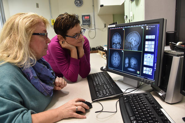 Washington University researchers Deanna Barch (left) and Joan Luby examine brain images for differences in gray matter.