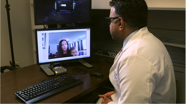 Dr. Shayan Vyas at Nemours Children's Hospital in Orlando meets with Alyssa Grimes and 5-year-old Zach via a Skype-like application.