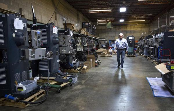 Chapin Cutler walks past a row of 70mm film projectors at Boston Light & Sound's offices in Boston. (Robin Lubbock/WBUR)