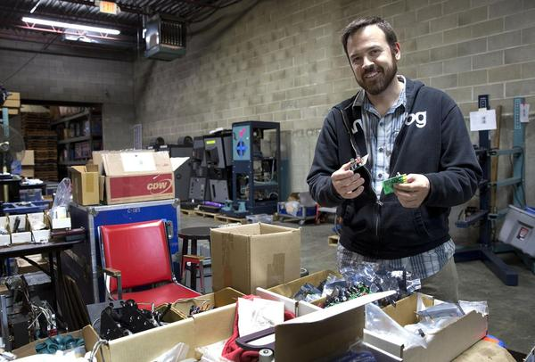 Dan Beatty looks in Boston Light & Sound warehouse for parts that are needed for a projector in Georgia. (Robin Lubbock/WBUR)