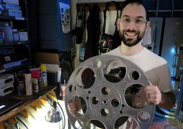 NIck Lazzarro, head projectionist at the Coolidge Corner Theatre, holds a 70 mm spool. (Andrea Shea/WBUR)