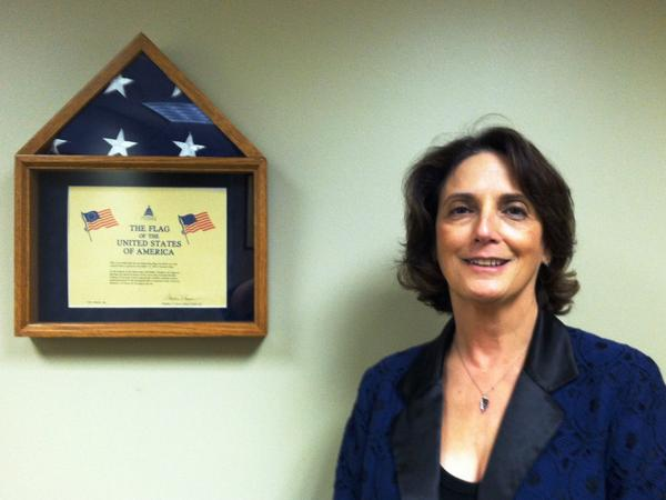 USF Associate Dean Rita D'Aoust stands next to the American Flag that was donated by U.S. Rep. Jeff Miller (R-FL) to the V-CARE student lounge at the College of Nursing.