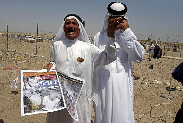 Relatives of Iraqi prisoners being held at Abu Ghraib denounce detainee treatment as they hold local newspapers featuring photos of U.S. soldiers abusing the prisoners inside the jail in May 2004.