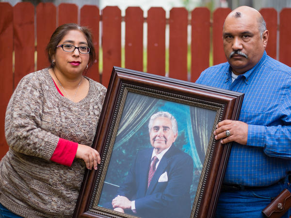 Patty Rodriguez and her brother Alex hold a photo of their father, Demetrio Rodriguez, who died in 2013.