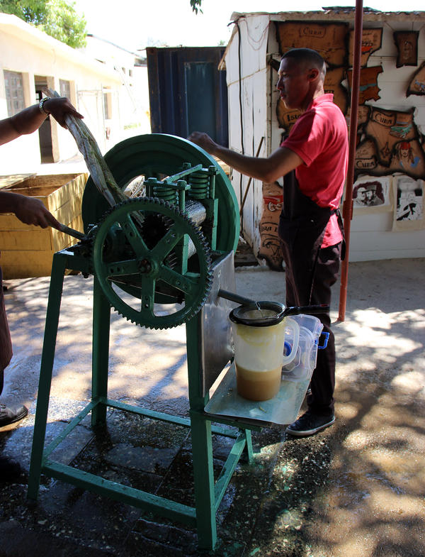 A worker presses cane juice for cold drinks at Finca Vigia