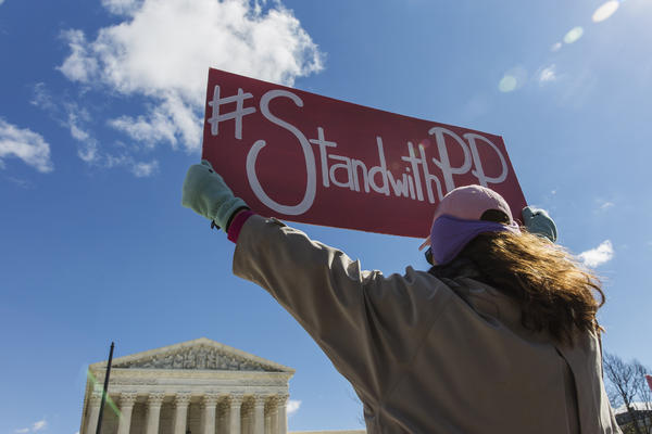 A protester shows her support for Planned Parenthood outside the Supreme Court Building in March