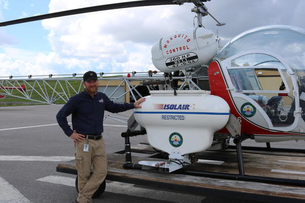 Rob Krueger standing in front of the Mosquito Control helicopter.