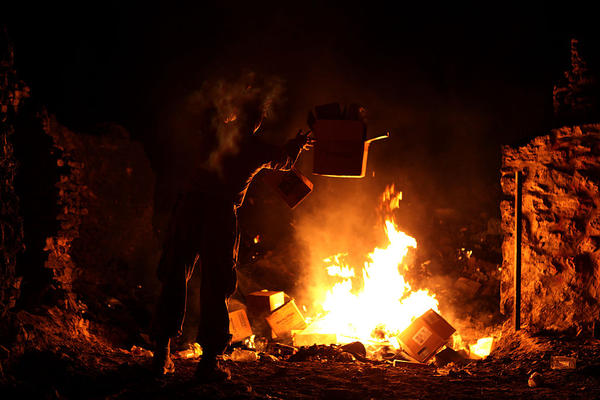Marine Lance Cpl. Richard Carmichael disposes of trash in a burn pit in Afghanistan in this 2013 photo.