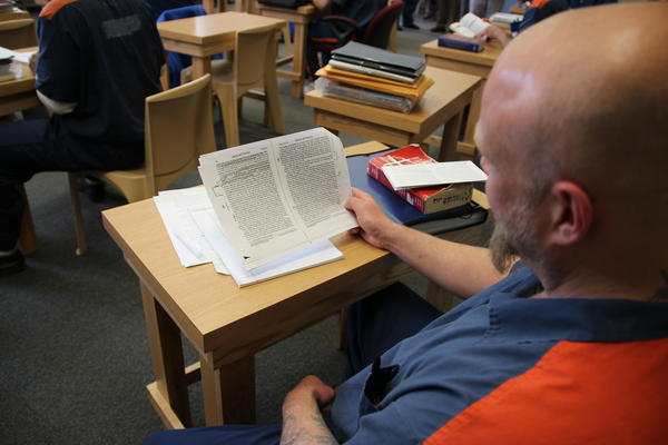 A student inmate reads in class.