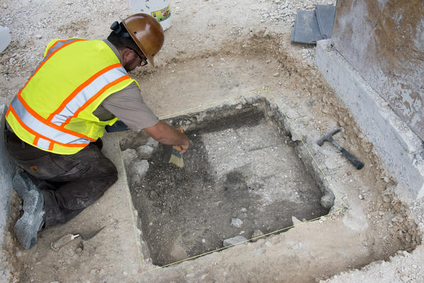 An archeologist at the Alamo brushes off dirt from adobe bricks believed to be from the 1700s