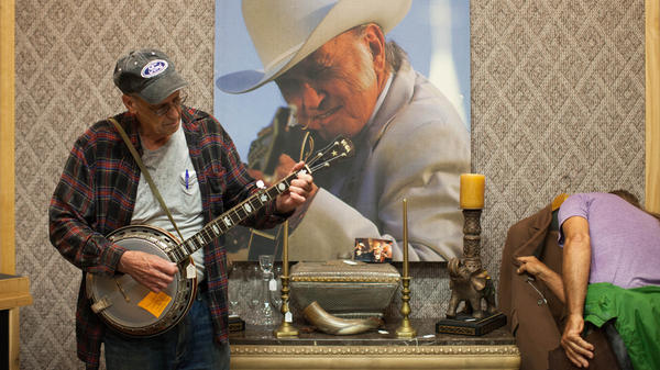 Prospective customers browse the effects at Bill Monroe's estate sale.