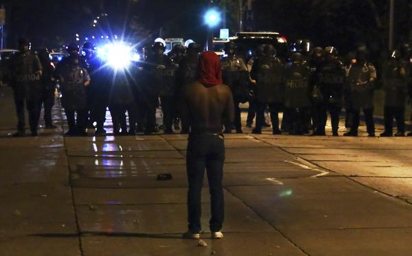 A protester faces police officers on Sunday in Milwaukee, during a protest held for Sylville Smith, who was shot and killed by a police officer as he reportedly attempted to flee during a traffic stop Saturday afternoon.