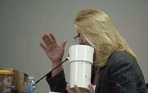 State Rep. Kathleen Peters holds a piece of a sewage line during Wednesday's meeting