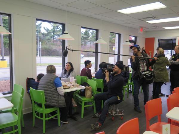 A crew films customer activity inside Holy Chicken.
