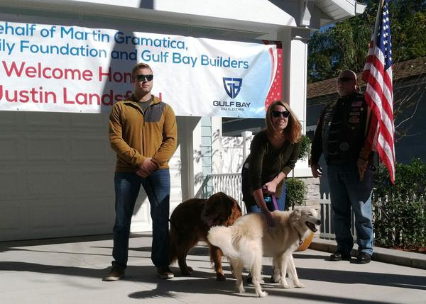 Justin Lansford and his wife, Carol, who raises service dogs, stand before a crowd of more than 50 people who came to their home dedication.