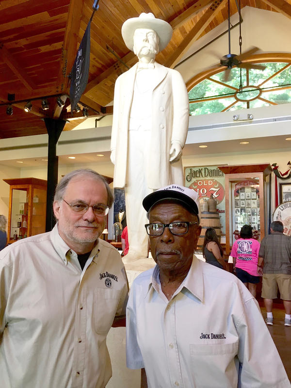 Company historian Nelson Eddy (left) stands in front of a statue of Jack Daniel with Claude Eady, a descendant of Nearis Green.