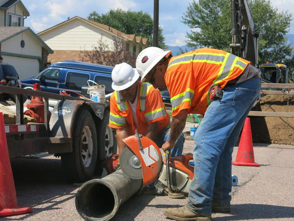 Construction workers prepare to cut a pipe for a new infrastructure project for the Security, Colo., Water and Sanitation District. The project is needed to ensure drinking water is 100 percent PFC free.