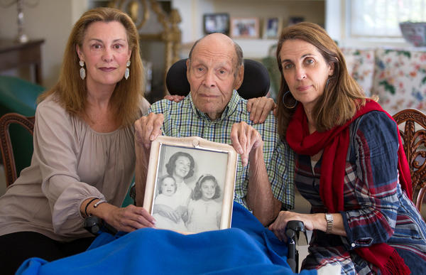 Laura Rees (left) and her sister Nancy Fee sit with their father, Joseph Fee, while holding a photo of his late wife, Elizabeth.