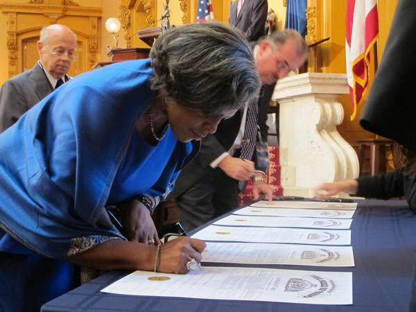 House Minority Leader Tracy Heard (D-Columbus) signs the documents recording her vote as an elector for President Barack Obama in the Statehouse in 2012.