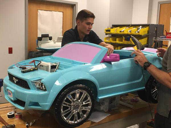 UNF mechanical engineering student Kristian Sipos works on a car for a young child with disabilities.